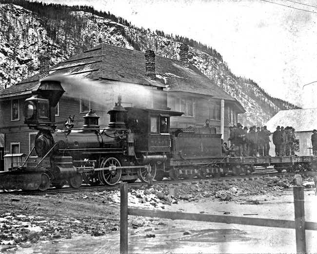 Steam engine in front of a large building in the winter