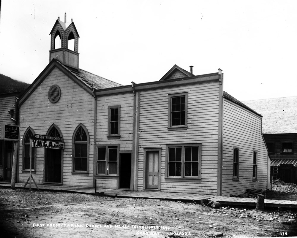 "Black and white image of church with sign reading ""Presbyterian Church, Y.M.C.A. free reading room"""