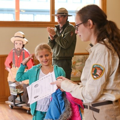 A volunteer ranger awards a young girl her junior ranger badge.