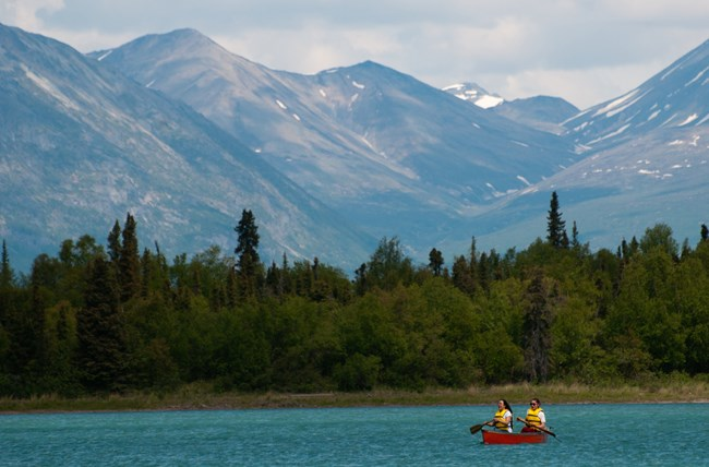 Two people canoeing on a lake with tall mountains in the background