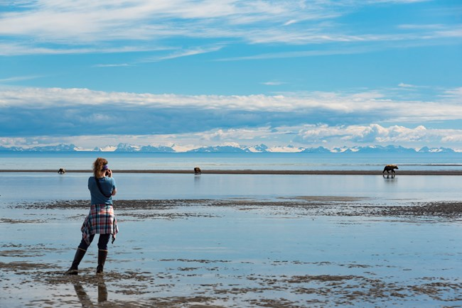 woman standing on mud flat photographing bear in distance.