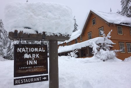 "Snow-covered sign reading ""National Park Inn"" in front of a building."