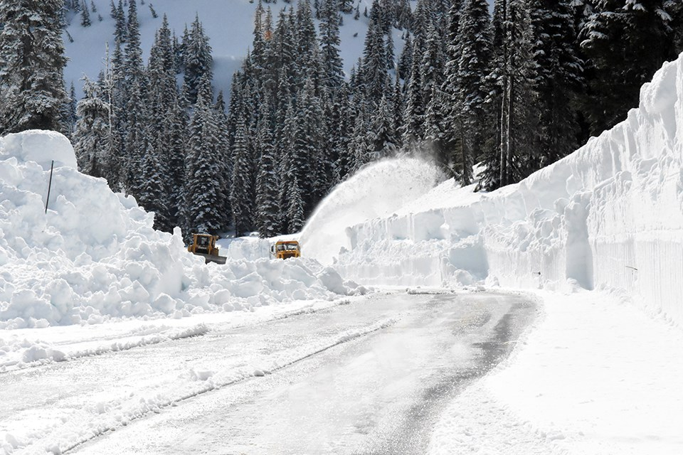 Two plows remove snow on partially covered road.