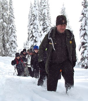 A ranger leads a group of people through  deep snow.