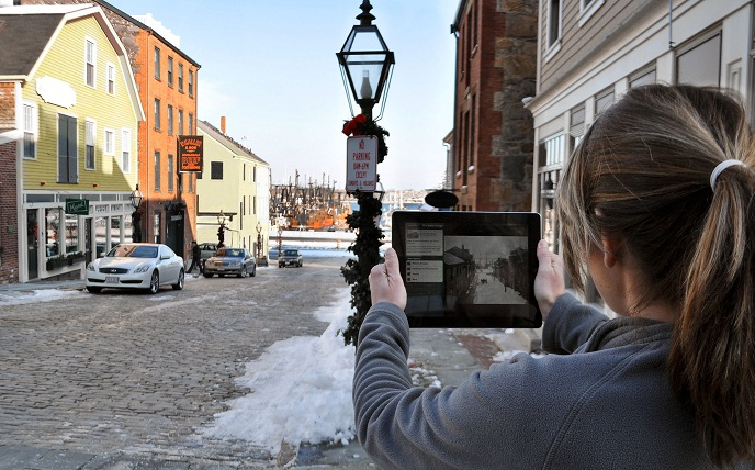 A young lady holds up an ipad with a historic view of Centre Street and actively compares it with the present day view in front of her.