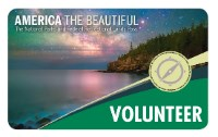 The 2019 Volunteer Pass appears with a rocky mountain, water and night sky