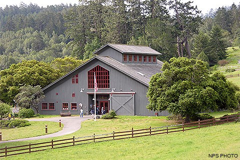 Visitors entering and exiting a gray barn-like visitor center surrounded by a fenced green pasture and trees.