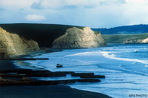 Sun-dappled, light-tan-colored cliffs on the left above a mostly sandy beach with waves washing ashore from the right.
