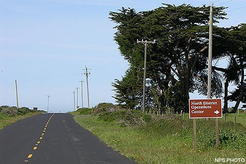 "A white on brown sign reading ""North District Operations Center"" alongside of a road."