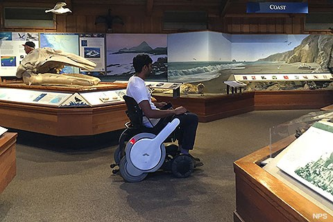 A person in a white motorized wheelchair among museum exhibits.