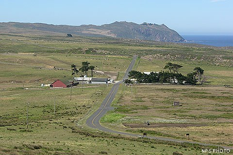 A narrow road winds through tan and green pastureland, through a cluster of buildings, and off toward a rocky headland on the edge of the ocean.