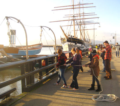 Students standing on Hyde Street Pier hauling on lines to raise a small boat up on davits.