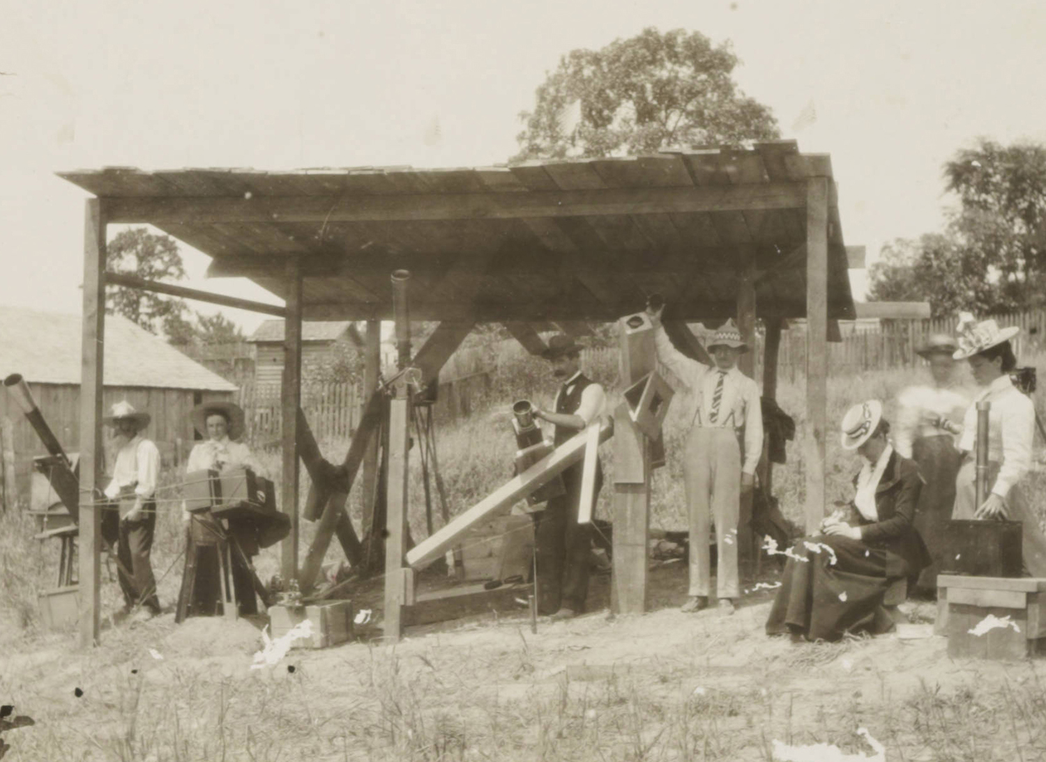 Photo 1: British Astronomical Association with their equipment in Wadesboro, NC. Black and white photo shows men and women in Victorian era clothing outside during daytime