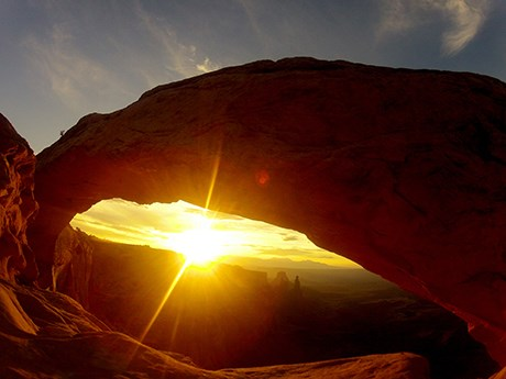 the sun's rays shine beneath a broad, silhouetted arch