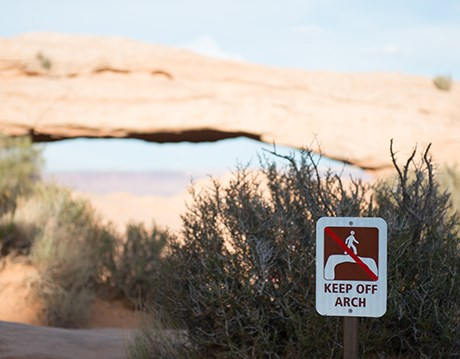 "a sign reading ""keep off arch"" with a broad arch in the background"