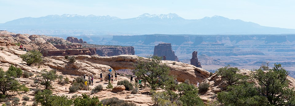 a group of people stand near an arch with distant mountains and canyons in the background