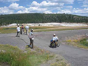 A visitor in a wheelchair visits the Old Faithful area.