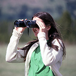 A young girl looking through binoculars.