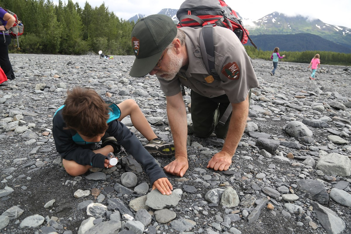 A ranger and a student investigate rocks in a river bed