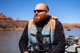 a man wearing a life jacket with a river in the background