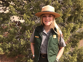 a park ranger stands in front of a juniper tree