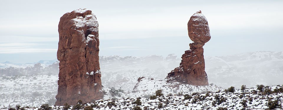 two red rock pinnacles in a snowy landscape
