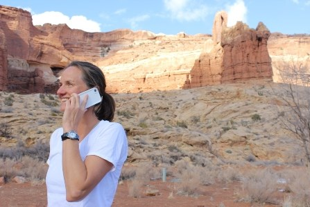 a woman standing in front of red rock pinnacles talks on a cell phone