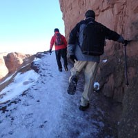 two hikers walk on a sloping, icy trail