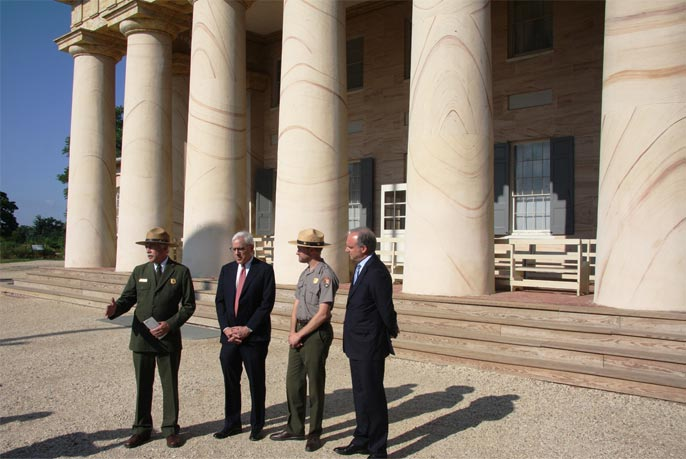 NPS Director Jon Jarvis, David Rubenstein, Brandon Bies, and National Park Foundation President and CEO Neil Mulholland stand before a row of columns at Arlington House.