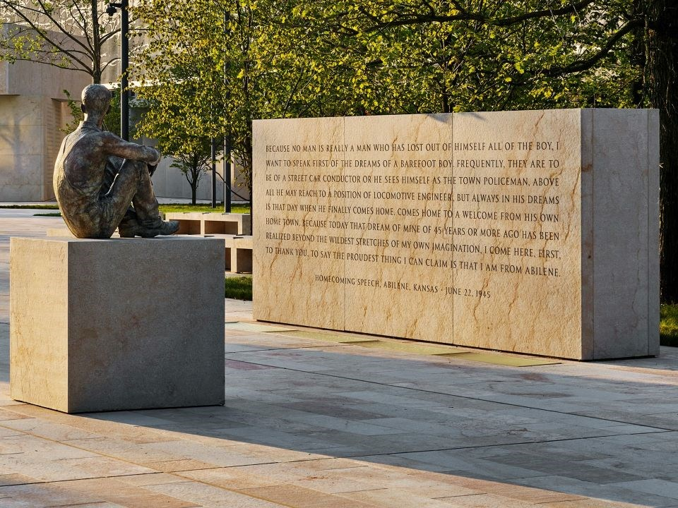 Statue of Dwight D. Eisenhower as a child sitting looking at a memorial wall with a long quote inscribed
