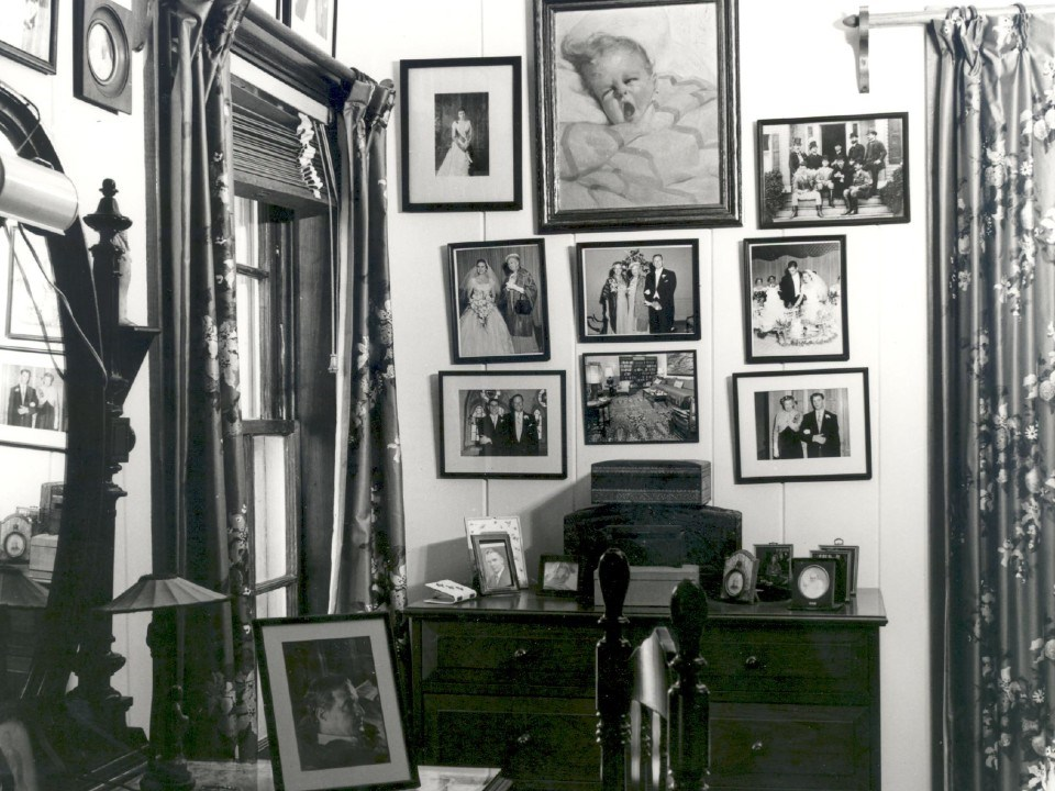 A corner of a furnished room with many framed photographs hanging on the walls.