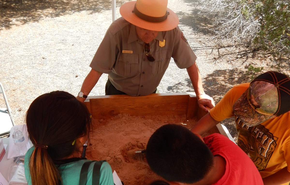 Ranger showing kids archeology tools in a mock excavation pit