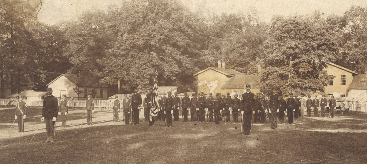 Black and white photo of soldiers standing at attention in a military barracks