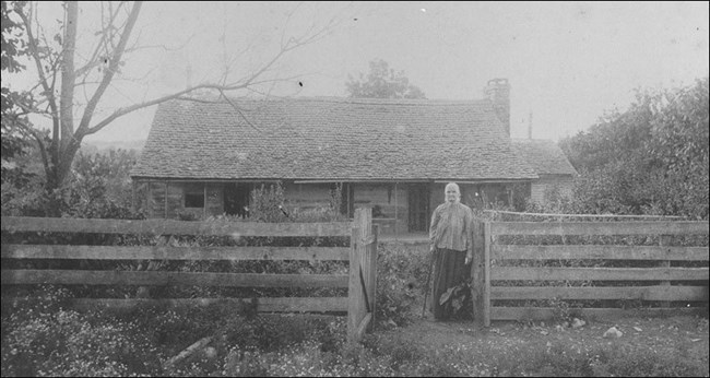 A woman standing in front of a house