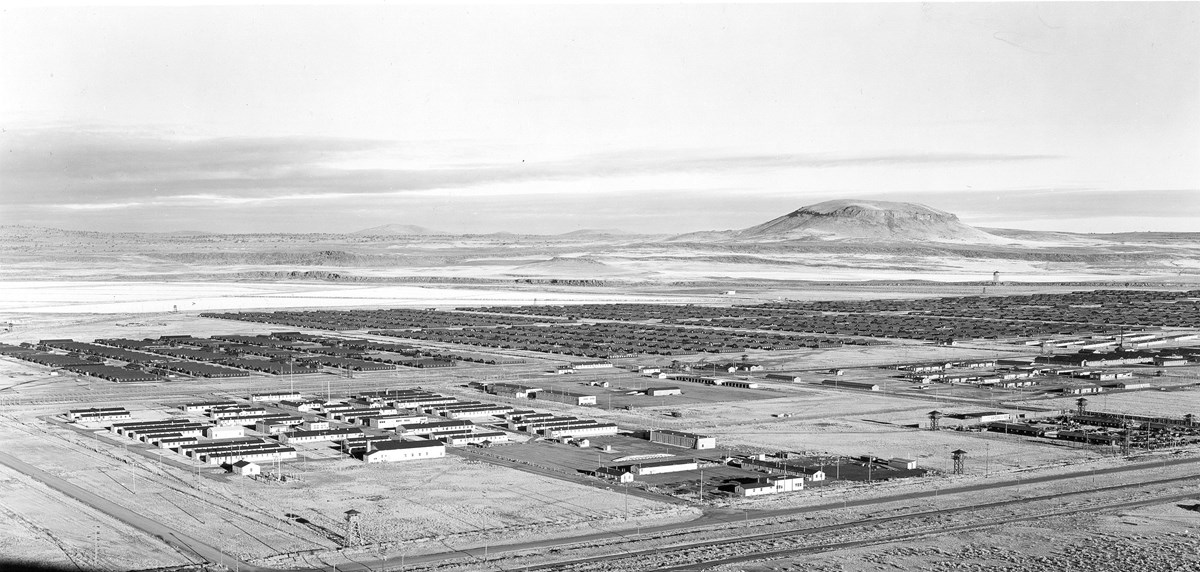 Historic black and white photo of a large camp complex in a high desert