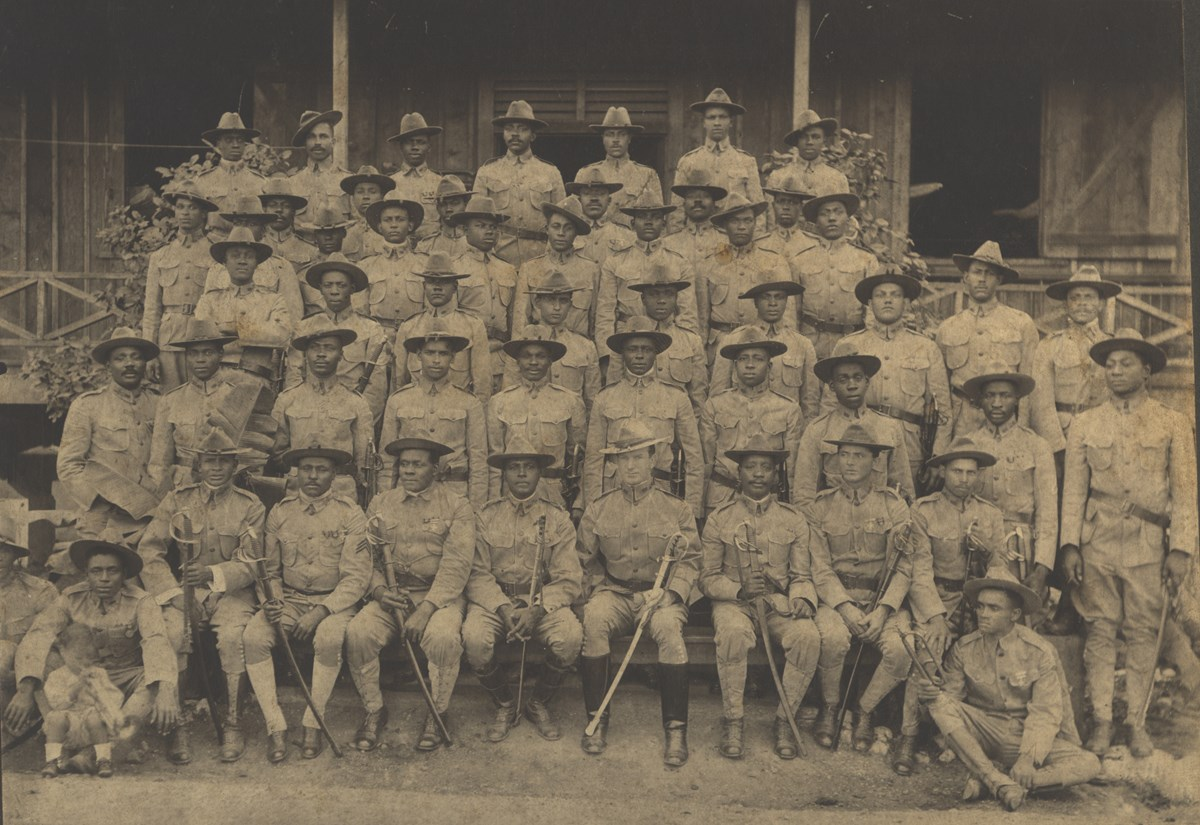 Historic black and white photo of a few lines of Buffalo Soldiers seated for a group picture