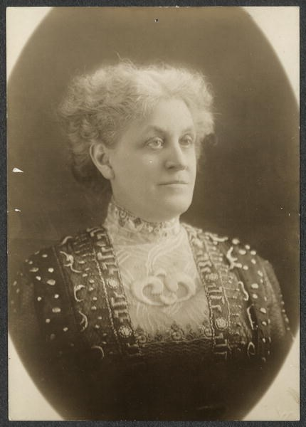 Formal portrait, head and shoulders, Carrie Chapman Catt, facing forward with head and eyes turned slightly to right, wearing a high-collared, richly brocaded or embroidered dress.