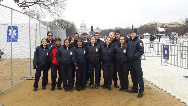 A group of teens wearing EMT uniforms stands along the National Mall with the capital in the background.