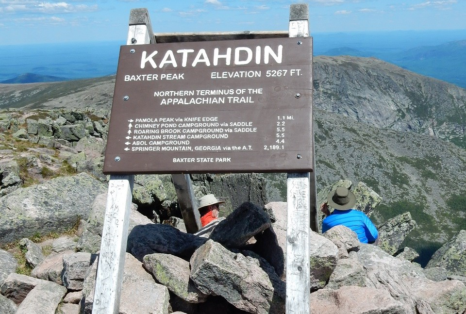 Backs of hikers behind a sign for Katahdin on a rocky mountain top