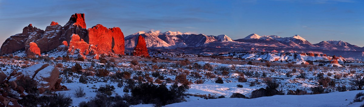 Lighting glow over snow-covered desert and rock formations