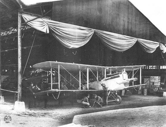 Biplane being assembled in a hangar