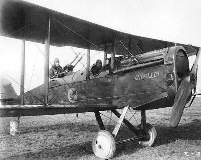 Biplane with pilot and gunner parked in a field
