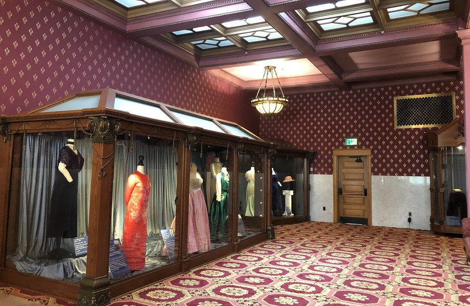 Museum exhibit with a line of historical dresses in glass cases