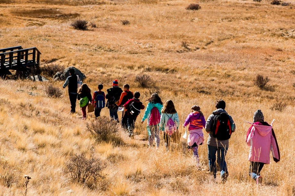 Line of kids hiking through a field