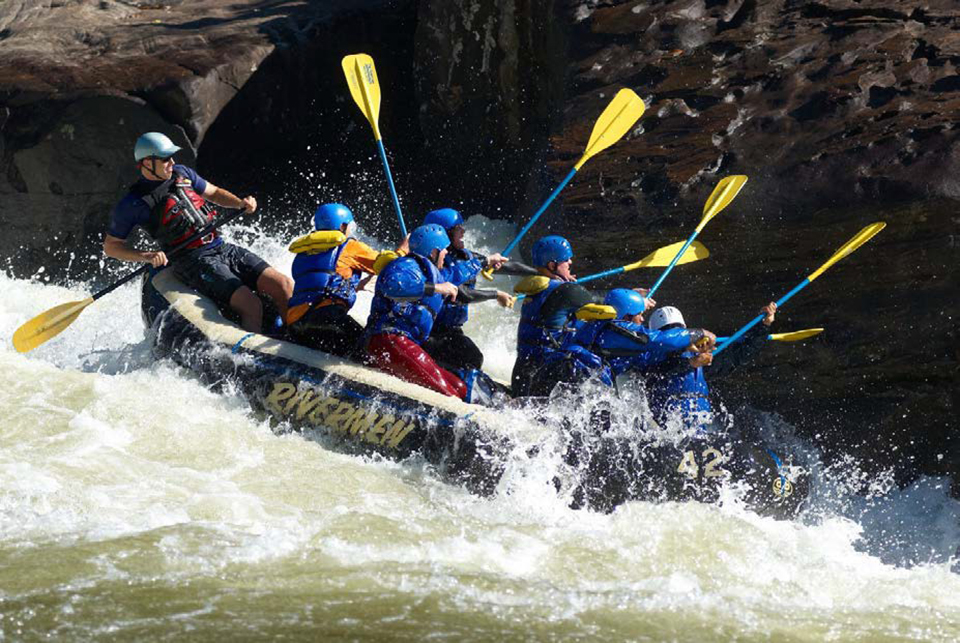 Group of paddlers holding paddles in the air to hit a rock