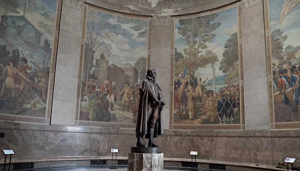 Statue of 18th century man in round memorial room surrounded by murals