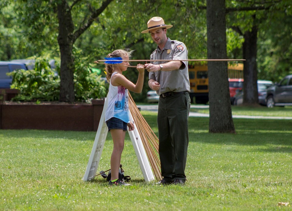 Ranger instructing kid on how to throw a spear using an atlatl