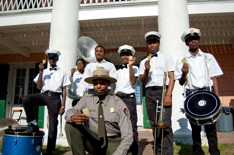 Ranger and youth brass band holding Junior Ranger badges