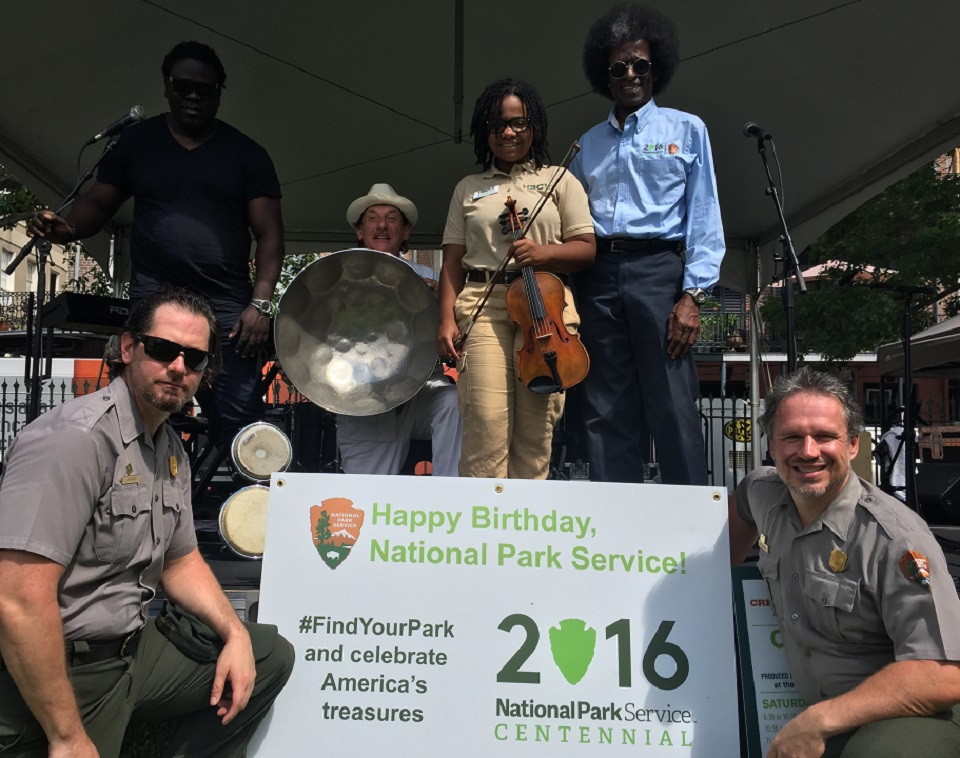 Park rangers and volunteers holding instruments and an NPS Centennial sign