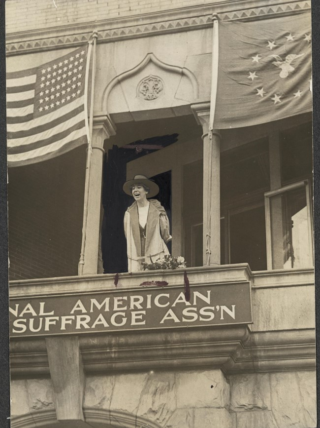 Altered photo of Jeannette Rankin on the balcony of NAWSA headquarters in Washington